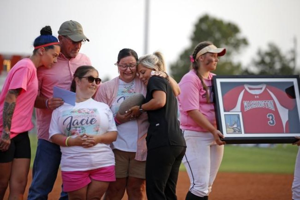 Photo -  Jay Stephens and Lea Ann Stephens, parents of the late Jacie Cochran, along with their other daughter Stephanie Stephens, are given a memorial stone by Kallie Hyde, right, and Madelyn Browning, from the Washington class of 2018, during a short presentation ceremony to honor Jacie Cochran after a softball game in Washington, Okla., Thursday, Sept. 17, 2020. Jacie died July 2 shortly after giving birth to her son Jaxon. [Bryan Terry/The Oklahoman]