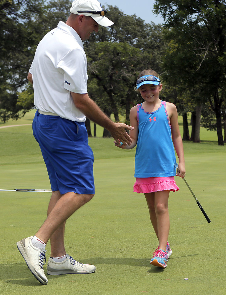 Photo -  Kate Melton and her father, Ryan, slap hands after a hole during the parent-child tournament at KickingBird Golf Course in Edmond. PHOTO BY SARAH PHIPPS, THE OKLAHOMAN   SARAH PHIPPS -