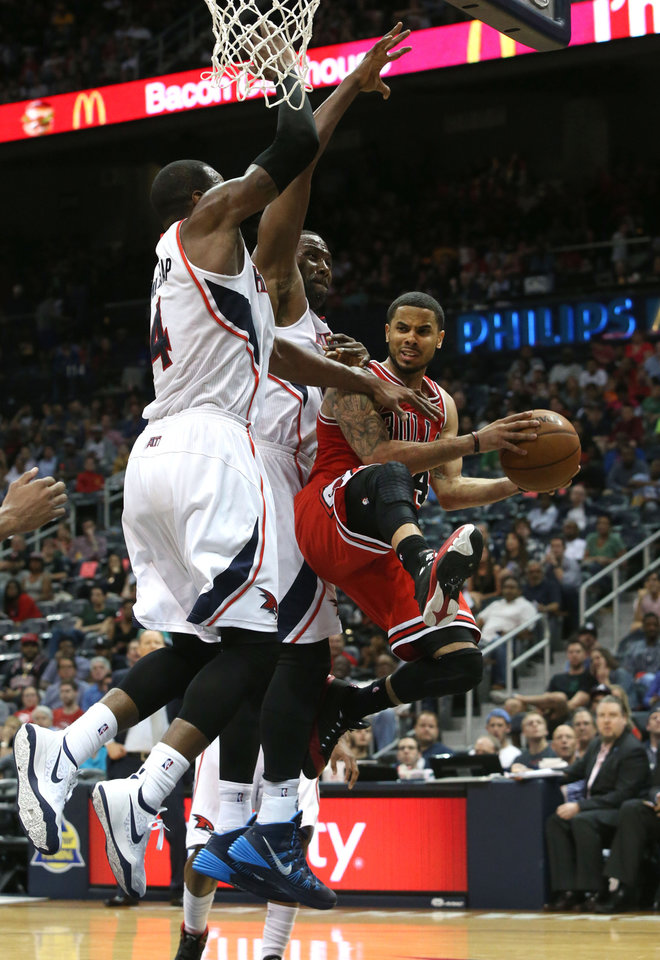 Photo - Chicago Bulls guard D.J. Augustin (14) looks to pass under the defense of Atlanta Hawks forwards Paul Millsap, left, and Elton Brand during the second half of an NBA basketball game Wednesday, April 2, 2014, in Atlanta. The Bulls won 105-92. (AP Photo/Jason Getz)