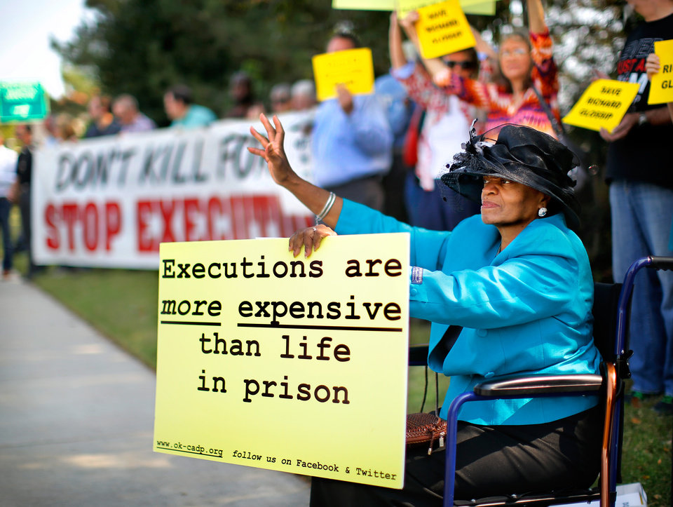 "Photo - Missionary Edna Osborne, 61, traveled with another woman from Broken Arrow to be among a crowd of peaceful protestors who gathered along NE 23 Street in front of the Governor's Mansion in Oklahoma City on  Wednesday, Sep. 30, 2015, to keep a silent vigil as the scheduled time drew near for the execution of convicted killer Richard Glossip at the state penitentiary in McAlester. Osborne said she is a Baptist ""and we don't believe in killing."" She added, ""the Bible tells us 'Thou shalt not kill' and because of her Christian beliefs, she felt it was important for her to attend the vigil. As many as 40 people held banners, waved signs and waved as honking motorists passed during their nearly two-hour long vigil.  Several groups were represented among the protestors, including the Oklahoma Coalition to Abolish the Death Penalty, The Norman community of Quakers and Amnesty International. Glossip, 52, received a last minute stay from Gov. Mary Fallin. He was scheduled to to die at 3 p.m. Wednesday after being convicted in two separate trials in the 1997 beating death of his boss, Barry Van Treese. Photo by Jim Beckel, The Oklahoman."