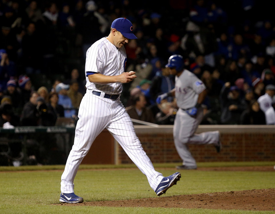 Chicago Cubs relief pitcher Shawn Camp returns to the mound after giving up a two-run home run to Texas Rangers' Adrian Beltre, background, which also scored Elvis Andrus, during the eighth inning of a interleague baseball game, Tuesday, April 16 2013, in Chicago. (AP Photo/Charles Rex Arbogast)