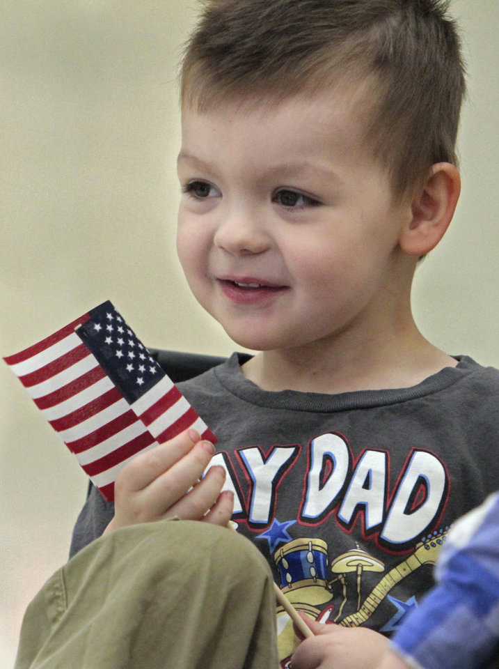 Trey Scott, 3, waits for his father, Spc. Galen Scott, to arrive as his dad and other members of the Oklahoma National Guard return from Afghanistan on Thursday, Jan. 12, 2012, in Norman, Okla.  His wife Jennifer is at right.
