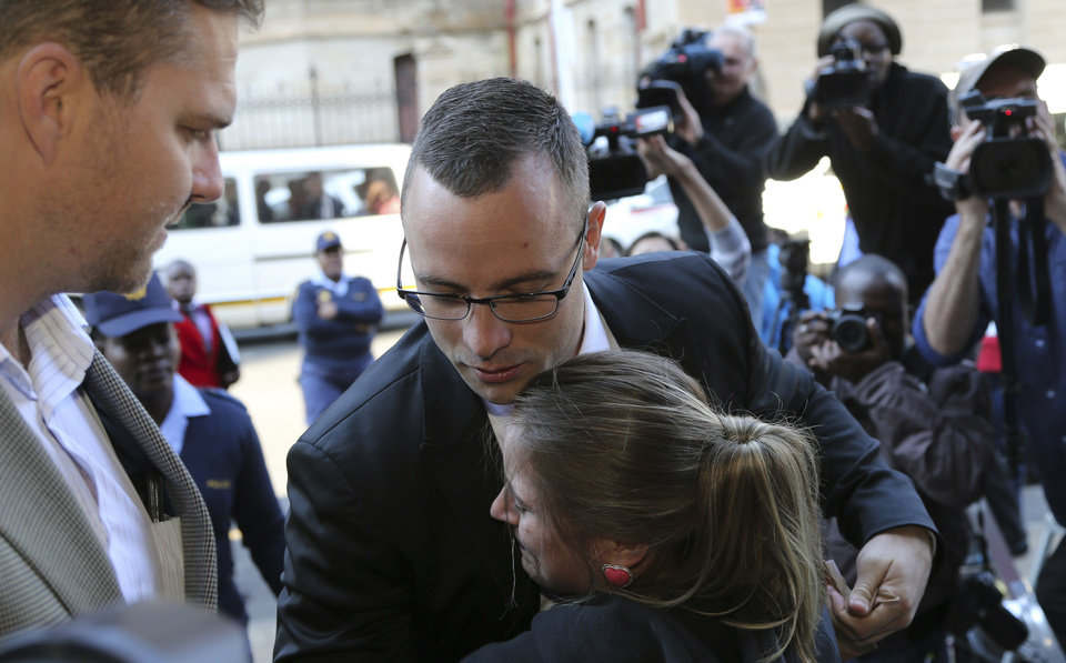 Photo - Oscar Pistorius, center top, receives a hug from his fan Kayla Nolan as he arrives at the high court in Pretoria, South Africa, Monday, May 5, 2014. Pistorius' murder trial enters a critical phase Monday as his defense team attempts to recover from a faltering start and reinforce the disabled athlete's claim that he fatally shot girlfriend Reeva Steenkamp by mistake because he was overwhelmed by a long-held fear of violent crime. (AP Photo/Themba Hadebe)