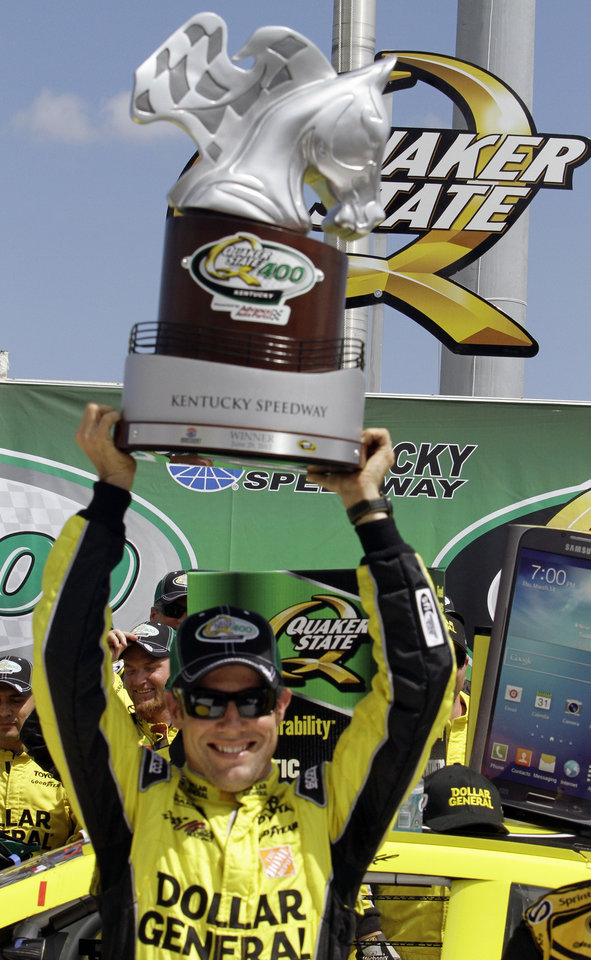 Photo - Matt Kenseth celebrates his victory in the NASCAR Sprint Cup auto race at Kentucky Speedway in Sparta, Ky., Sunday, June 30, 2013 by hoisting the trophy above his head in the winner's circle.  (AP Photo/Garry Jones)