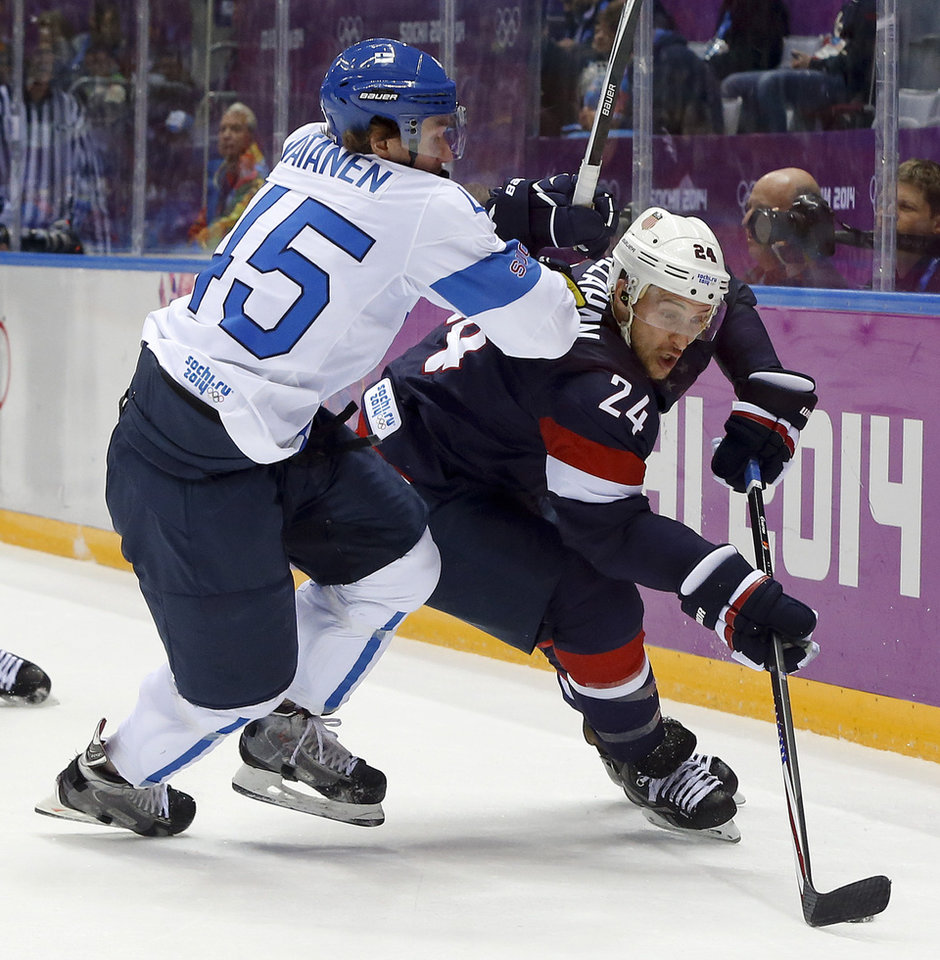 Photo - Finland defenseman Sami Vatanen challenges USA forward Ryan Callahan for the puck during the first period of the men's bronze medal ice hockey game at the 2014 Winter Olympics, Saturday, Feb. 22, 2014, in Sochi, Russia. (AP Photo/Mark Humphrey)