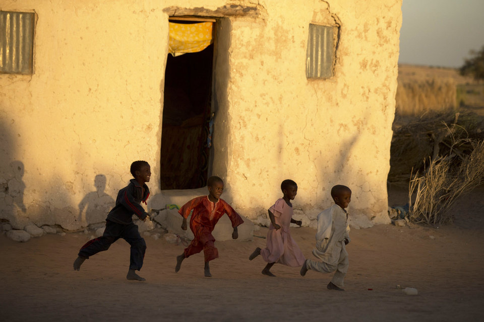 In this Nov. 1, 2012 photo, seven-year-old Achta, second right, plays with Nasruddin, right, Mahamat, second left, and her big brother, in front of her family's one-room house in Louri village, in the Mao region of Chad. Achta's birth seven years ago coincided with the first major drought to hit the Sahel this decade. Climate change has meant that the normally once-a-decade droughts are now coming every few years. The droughts decimated her family's herd. With each dead animal, they ate less. (AP Photo/Rebecca Blackwell) ORG XMIT: NY884
