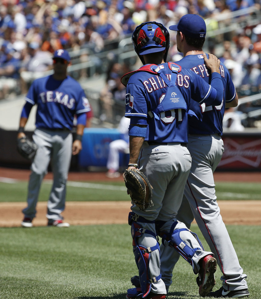 Photo - Texas Rangers catcher Robinson Chirinos (61) consoles starting pitcher Nick Tepesch (23) who allowed five runs in the first inning of a baseball game against the New York Mets in New York, Sunday, July 6, 2014. (AP Photo/Kathy Willens)