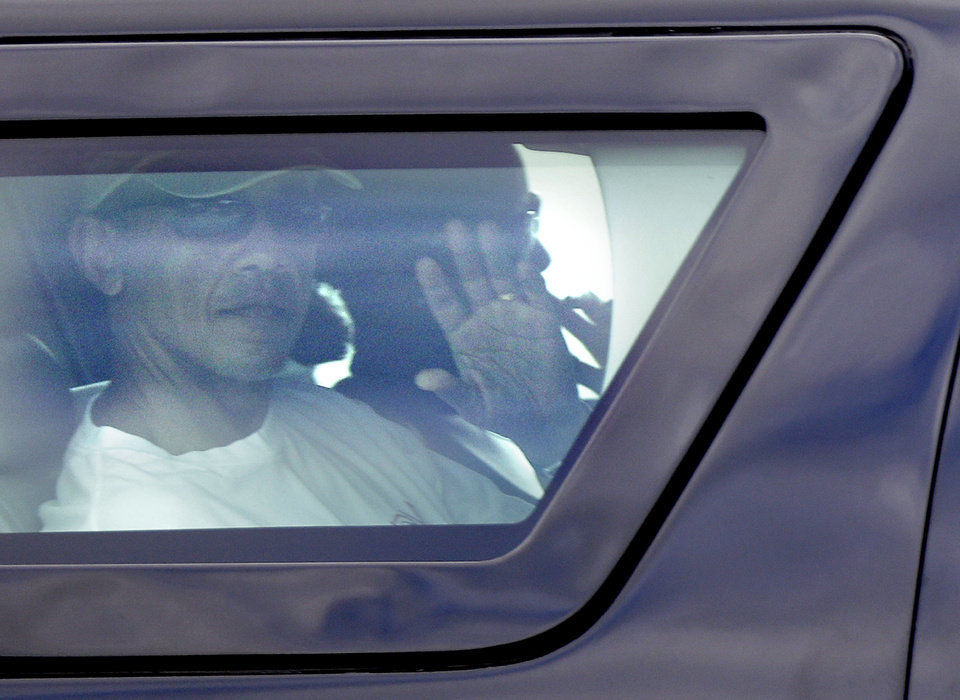 Photo - President Barack Obama waves from the window of his motorcade vehicle as he returns from golf and a walk on the beach with his family at Marine Corp Base Hawaii, in Kailua, Hawaii, Wednesday, Dec. 26, 2012. The president and the first family are in Hawaii for a family holiday vacation. (AP Photo/Gerald Herbert)