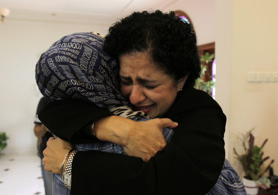 Photo -   Dr. Rula al Saffar, right, and Dr. Fatima Haji, left, comfort each other on getting word of a judge's verdict Thursday, June 14, 2012, at a fellow doctor's home in Sehla, Bahrain, west of the capital Manama. A defense lawyer in Bahrain says a court has sentenced nine medical professionals to prison terms ranging from five years to one month in a retrial on charges of aiding the Gulf kingdom's uprising.(AP Photo/Hasan Jamali)
