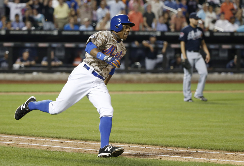 Photo - New York Mets Curtis Granderson runs on an eighth-inning, solo home run off Atlanta Braves relief pitcher Luis Avilan, right, in a baseball game in New York, Monday, July 7, 2014. (AP Photo/Kathy Willens)