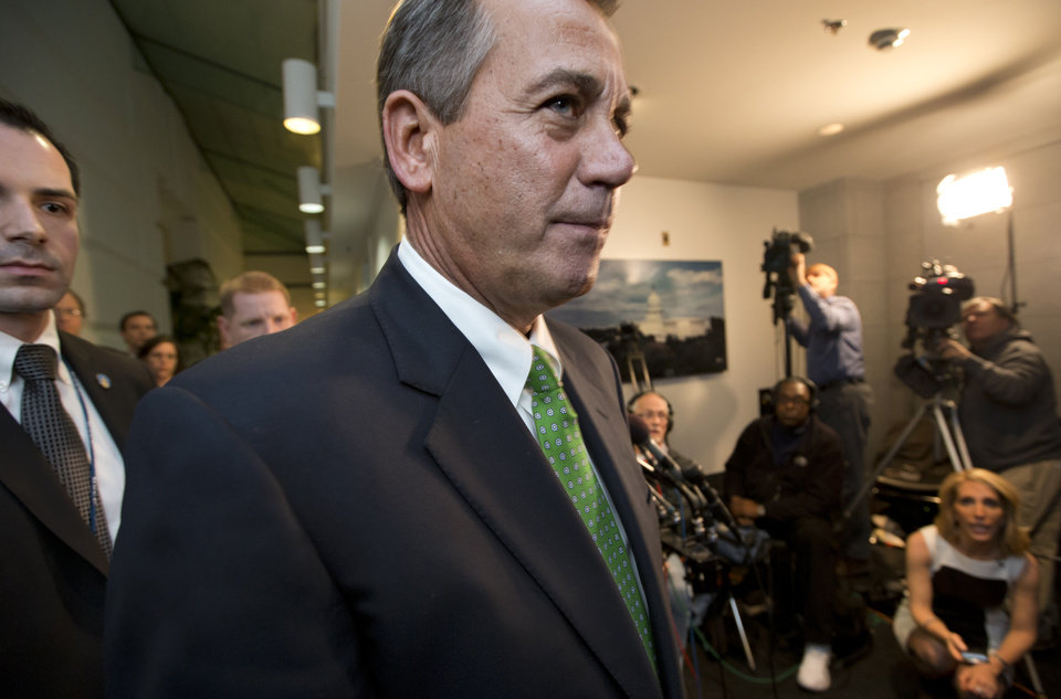 Photo - Speaker of the House John Boehner, R-Ohio, passes waiting reporters as he leaves a closed-door GOP meeting on the