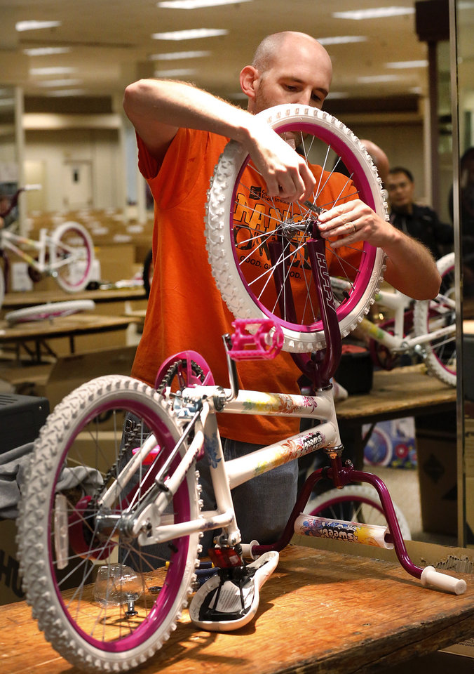 Joe Thomason of Moore tightens the nuts on a front tire as nears the completion of this bicycle assembly. This is his fourth year to volunteer with the project. Thomason is a member of the Tinker Cycling Club. More than 150 volunteers donated their time and skills Saturday morning, Dec. 1, 2012, assembling 830 childrens\' bicycles for the Salvation Army\'s bike giveaway project. The bicycles will be distributed to children in need at Christmas. Bikes were assembled inside the former J.C. Penney store in the vacant Crossroads Mall. Photo by Jim Beckel, The Oklahoman