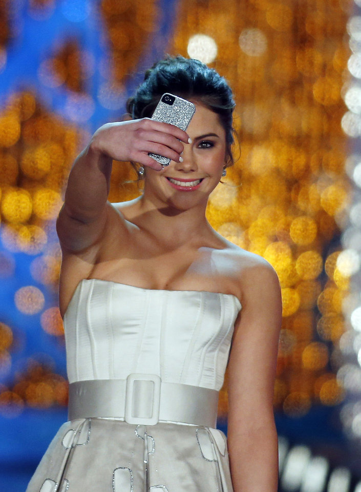 Photo - Miss America judge McKayla Maroney photographs herself onstage before the pageant on Saturday, Jan. 12, 2013, in Las Vegas. (AP Photo/Isaac Brekken)