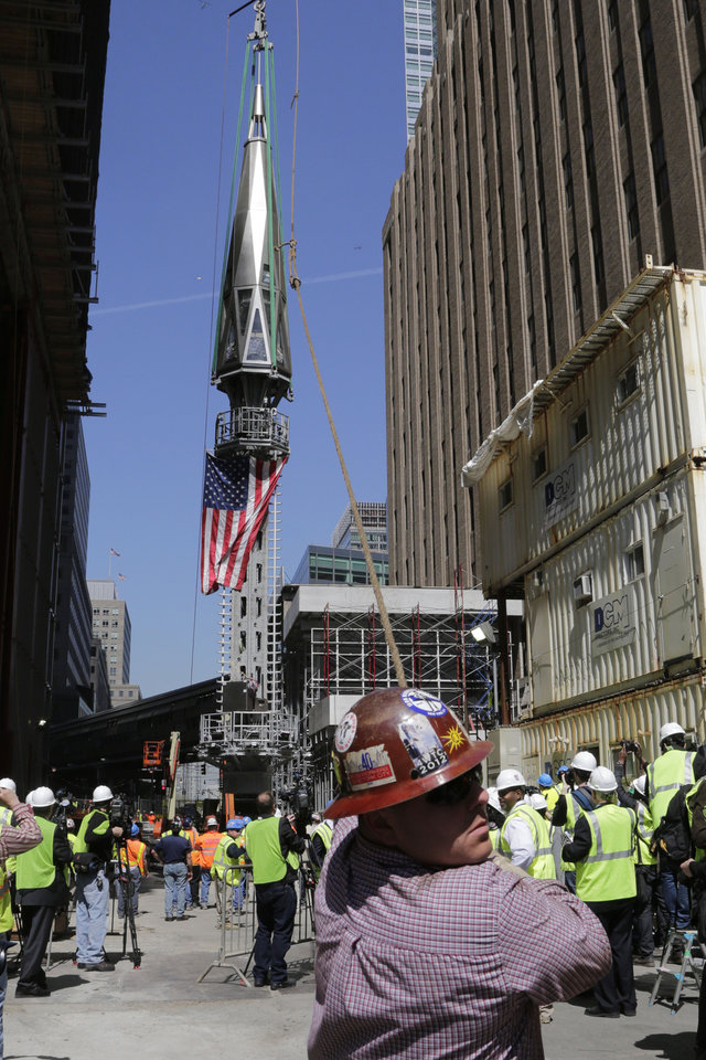 Photo - A worker holds a guide rope as the final piece of spire is hoisted to the roof of One World Trade Center, Thursday, May 2, 2013 in New York.  The piece will be attached to the spire at a later date, capping off the tower at 1,776 feet. (AP Photo/Mark Lennihan)