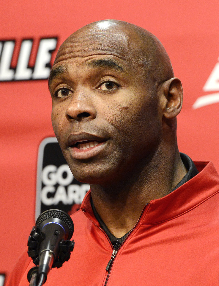 Photo - Louisville head football coach Charlie Strong answers a reporters question during a press conference Thursday, Dec. 6, 2012, in Louisville, Ky. Strong announced this morning that he has turned down the head coaching job offer from the University of Tennessee and will stay at Louisville. (AP Photo/Timothy D. Easley)