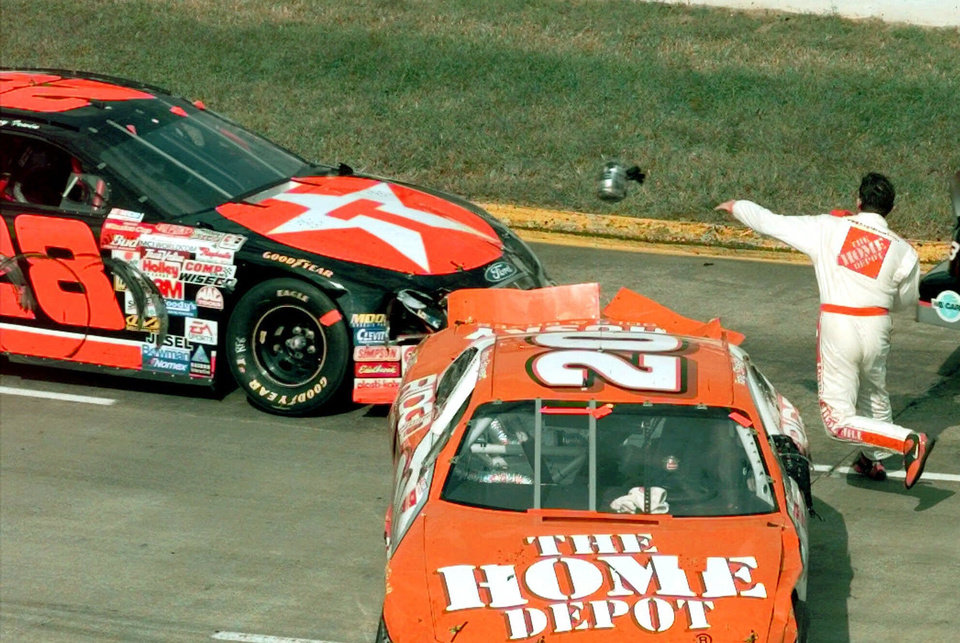 Photo - FILE - In this Oct. 3, 1999, file photo, Tony Stewart throws a piece of equipment in the direction of the car of Kenny Irwin (28) after leaving his wrecked car, right, in turn one of the Martinsville Speedway during the NAPA AutoCare 500 in Martinsville, Va. NASCAR added a rule Friday, Aug. 15, 2014, ordering drivers to not approach the track or moving cars after accidents. (AP Photo/Steve Helber, File)