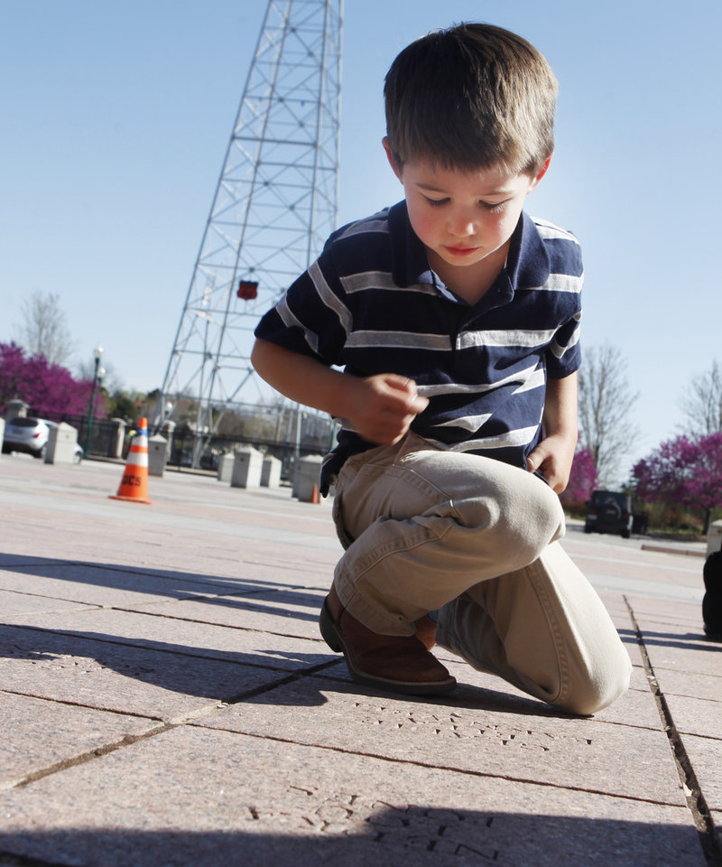 Photo -  Beckett Barnwell, a great-grandchild of Gladie Barnwell, looks over her paver at the state Capitol. Photo by K.T. King, The Oklahoman   KT King -