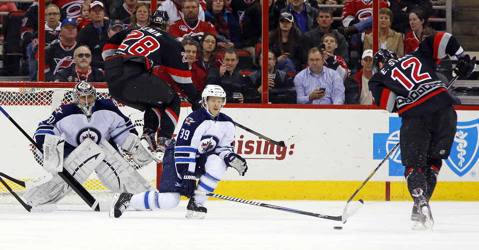 Photo - Carolina Hurricanes' Alexander Semin (28) of Russia, jumps over Winnipeg Jets goalie Ondrej Pavelec (31) of the Czech Republic, as the Hurricanes' Eric Staal (12) fires the puck at the Jets' Tobias Enstrom (39) of Sweden, during the first period of an NHL hockey game, Tuesday, March 26, 2013, in Raleigh, N.C. (AP Photo/Karl B DeBlaker)