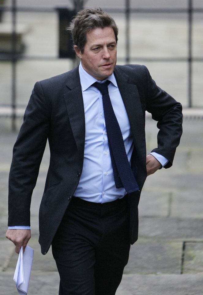 Photo - FILE - This is a Monday, Nov. 21, 2011 file photo of  British actor Hugh Grant as he arrives to give evidence at the the Leveson inquiry in London. Celebrities including author J.K. Rowling and actor Hugh Grant are accusing the government of letting down victims of media intrusion. They are urging lawmakers to back new measures to rein in Britain's unruly press. (AP Photo/Alastair Grant, File)