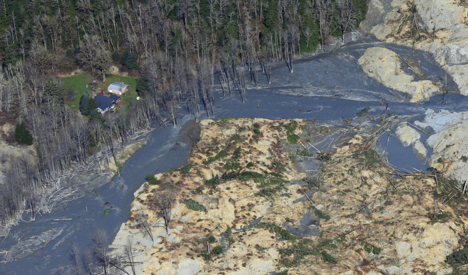 Photo - An intact house sits at left at the edge of the massive mudslide that killed at least eight people and left dozens missing is shown in this aerial photo, Monday, March 24, 2014, near Arlington, Wash. The search for survivors grew Monday, raising fears that the death toll could climb far beyond the eight confirmed fatalities. (AP Photo/Ted S. Warren)