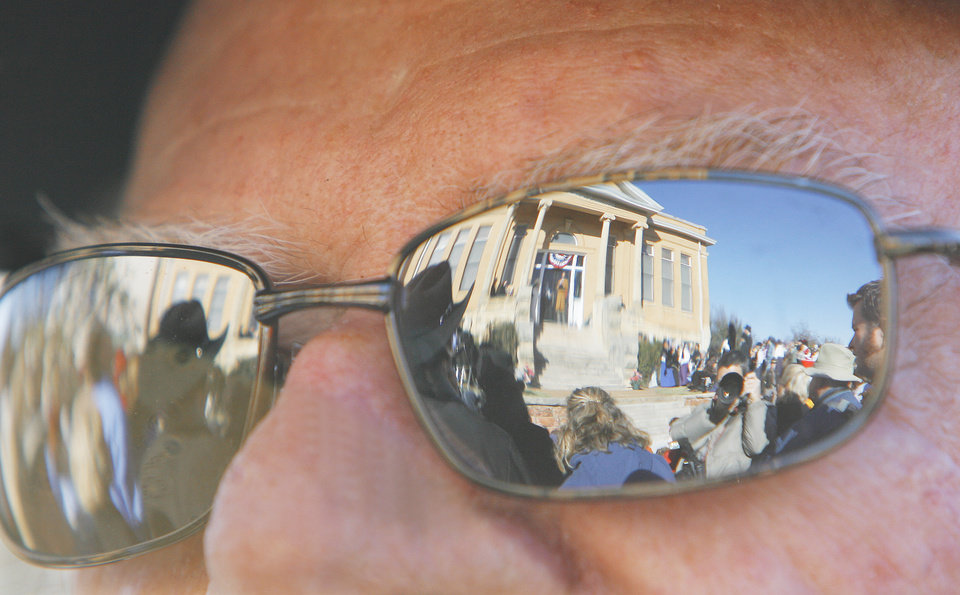 Photo - Bob Blackburn and the Carnegie Library are reflected in the sunglasses of Noel Kurger, from OKC, as he watches the centennial festivities in Guthrie, Friday, November 16, 2007.   By David McDaniel, The Oklahoman