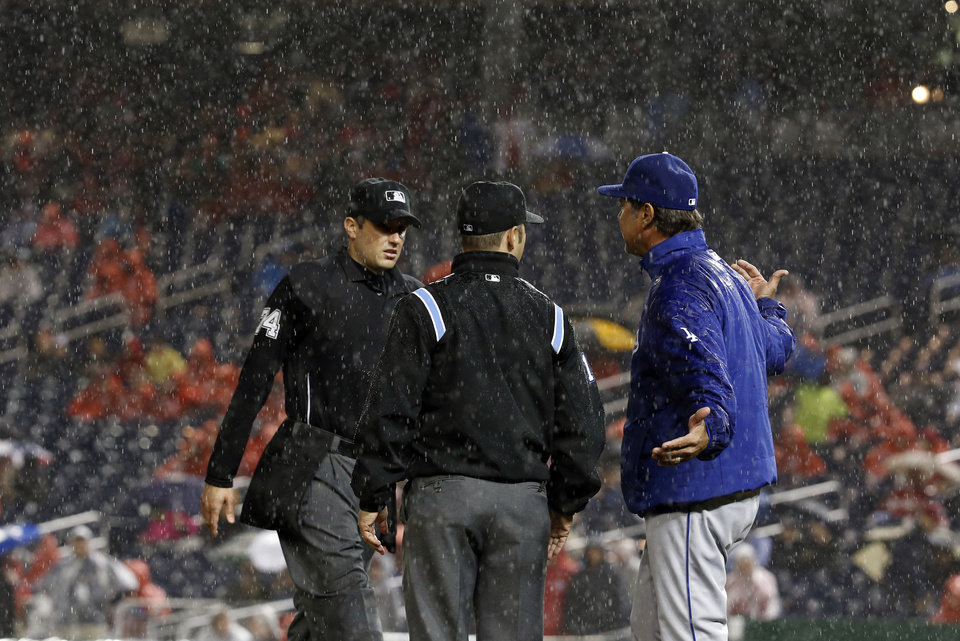 Photo - Umpire John Tumpane, left, and umpire Mark Wegner listen to Los Angeles Dodgers manager Don Mattingly (8) as he comes out during the fourth inning of a baseball game against the Washington Nationals at Nationals Park, Monday, May 5, 2014, in Washington. The game is rain delayed in the fourth inning. (AP Photo/Alex Brandon)