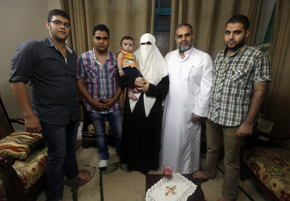 Photo - In this Tuesday, June 25, 2013, members of the Rantisi family pose for a photo at their house in Gaza City. From right are Baraa, 23, Mohammed, his father, 55, Kifah, his mother, 47, Mohammed, Baraa's 10-month-old son, Malik, 18, and Anaz, 22. On the day of his induction, Baraa Rantisi was told to wait near a mosque. A white car drove up. Secret passwords were exchanged. And then he was sworn into the Muslim Brotherhood, an exclusive movement that sees itself on a divine mission to establish Islamic rule. AP reporters got rare access to the Rantisi family, the closest thing to a royal clan in the Brotherhood in Gaza, at a time when the movement is under siege throughout the region. (AP Photo/Hatem Moussa)