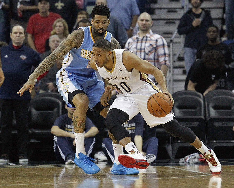 Photo - New Orleans Pelicans shooting guard Eric Gordon (10) works around Denver Nuggets small forward Wilson Chandler in the first half of an NBA basketball game in New Orleans, Sunday, March 9, 2014. (AP Photo/Bill Haber)