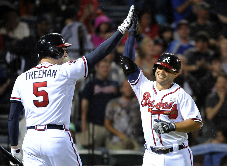 Photo - Atlanta Braves' Tommy La Stella, right, is congratulated by Freddie Freeman after his solo home run against the Washington Nationals during the fifth inning of a baseball game Friday, Aug. 8, 2014, in Atlanta. (AP Photo/David Tulis)