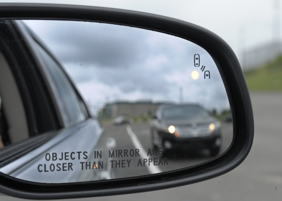 Photo -   In this photo taken Tuesday, May 22, 2012, professional test driver J.D. Ellis of Cincinnati, Ohio, demonstrates the side mirror warning signal in a Ford Taurus at an automobile testing area in Oxon Hill, Md. The display at a recent transportation conference was a peek into the future of automotive safety: cars that to talk to each other and warn drivers of impending collisions. Later this summer, the government is launching a yearlong, real-world test involving nearly 3,000 cars, trucks and buses using volunteer drivers in Ann Arbor, Mich. (AP Photo/Susan Walsh)