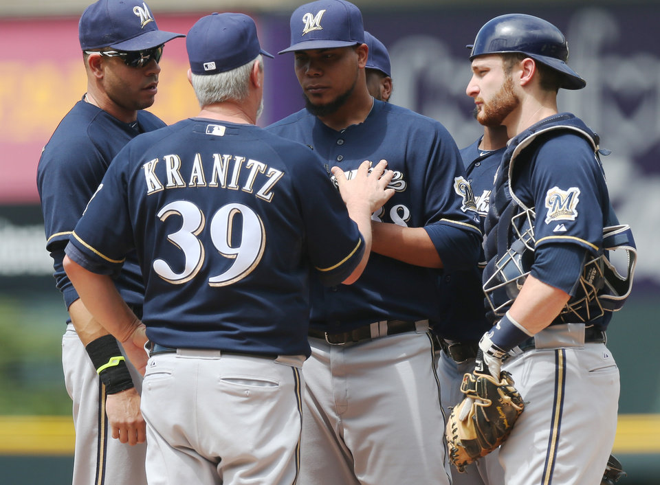 Photo - Milwaukee Brewers pitching coach Rick Kranitz (39) confers with starting pitcher Wily Peralta, third from left, as third baseman Aramis Ramirez, left, and catcher Jonathan Lucroy, right, look on after Peralta gave up a single to allow in two runs to Colorado Rockies' Justin Morneau in the first inning of a baseball game in Denver, Saturday, June 21, 2014. (AP Photo/David Zalubowski)