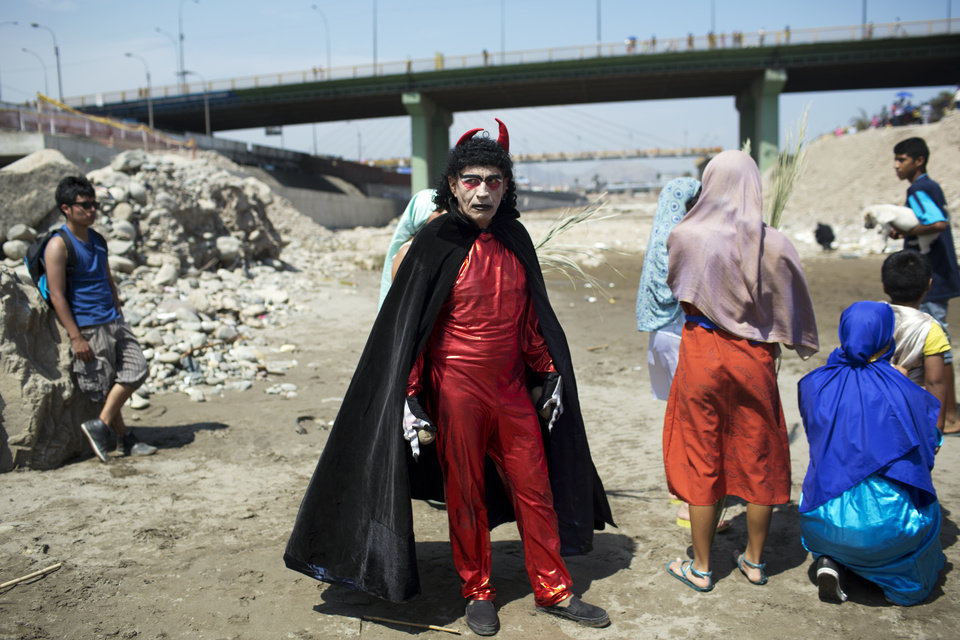 Photo - An actor dressed in a devil costume stands on the shores of the Rimac River in Lima, Peru, Thursday, April 17, 2014. The actor performed for people after they attended the reenactment of Jesus' baptism in the river as part of during Holy Week celebrations. (AP Photo/Rodrigo Abd)