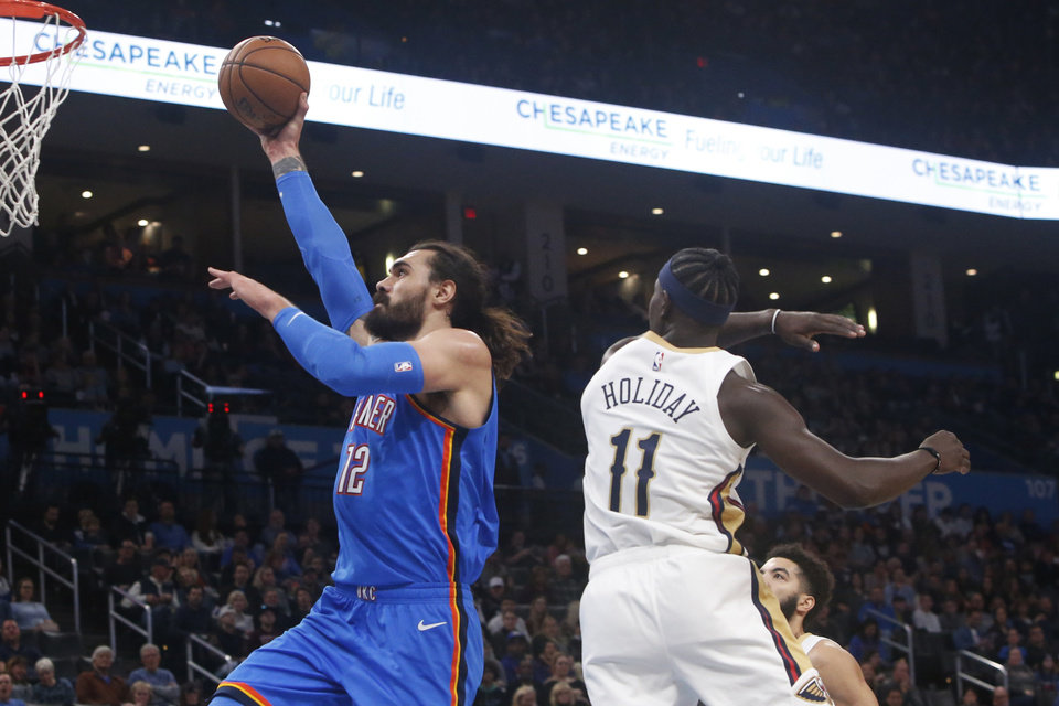 Photo - Oklahoma City Thunder center Steven Adams (12) goes up for a dunk past New Orleans Pelicans guard Jrue Holiday (11) during the first half of an NBA basketball game Friday, Nov. 29, 2019, in Oklahoma City. [AP Photo/Sue Ogrocki]