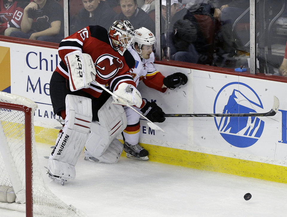 Photo - New Jersey Devils goalie Cory Schneider (35) checks Calgary Flames' Bryce Van Brabant (48) into the boards during the second period of an NHL hockey game in Newark, N.J., Monday, April 7, 2014. (AP Photo/Mel Evans)