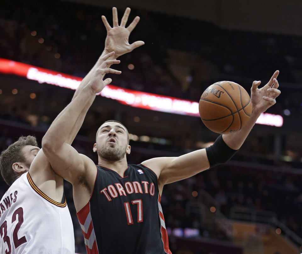 Photo - Toronto Raptors' Jonas Valanciunas (17), from Lithuania, loses control of the ball as Cleveland Cavaliers' Spencer Hawes (32) defends during the first quarter of an NBA basketball game Tuesday, March 25, 2014, in Cleveland. (AP Photo/Tony Dejak)