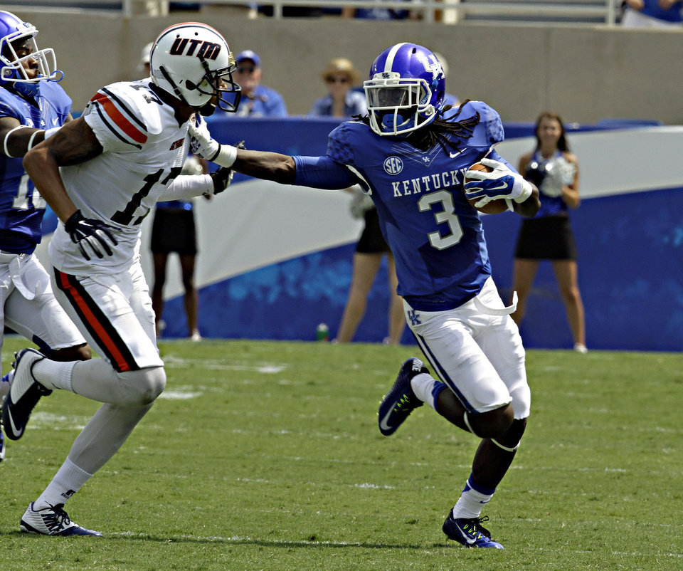 Photo - Kentucky cornerback Fred Tiller (3) fends off Tennessee-Martin wide receiver Kyle Kerrick (17) after making a pass interception in their NCAA college football game in Lexington, Ky., Saturday, Aug. 30, 2014. Kentucky beat Tennessee-Martin 59-14 to open the season. (AP Photo/Garry Jones)