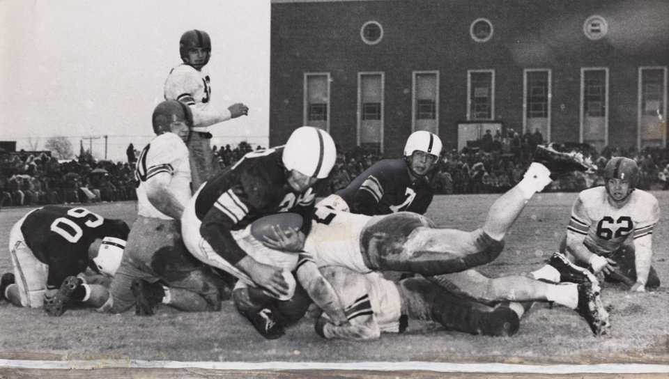 Photo - Lindell Pearson scores Oklahoma's first touchdown in the Sooners' 19-15 win over then-Oklahoma A&M in Stillwater. The Sooner in the background is Homer Paine. At right is Aggie guard Wayne Burrow (62). Staff photo taken Nov. 27, 1948.