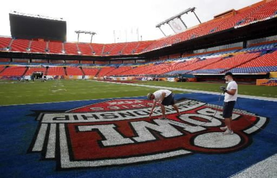Photo - Stadium workers spray paint an end zone at Dolphin Stadium in Miami today. AP Photo