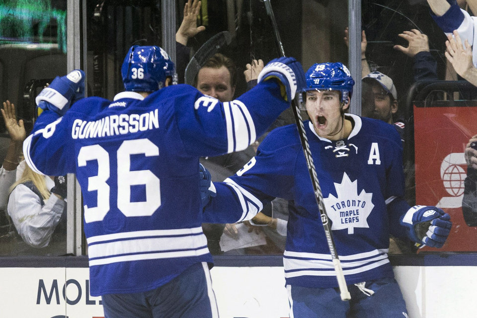 Toronto Maple Leafs\' Joffrey Lupul, right, turns to celebrate with teammate Carl Gunnarsson after scoring the game winning goal against Philadelphia Flyers during overtime of an NHL hockey game, Saturday, March 8, 2014 in Toronto. (AP Photo/The Canadian Press, Chris Young)