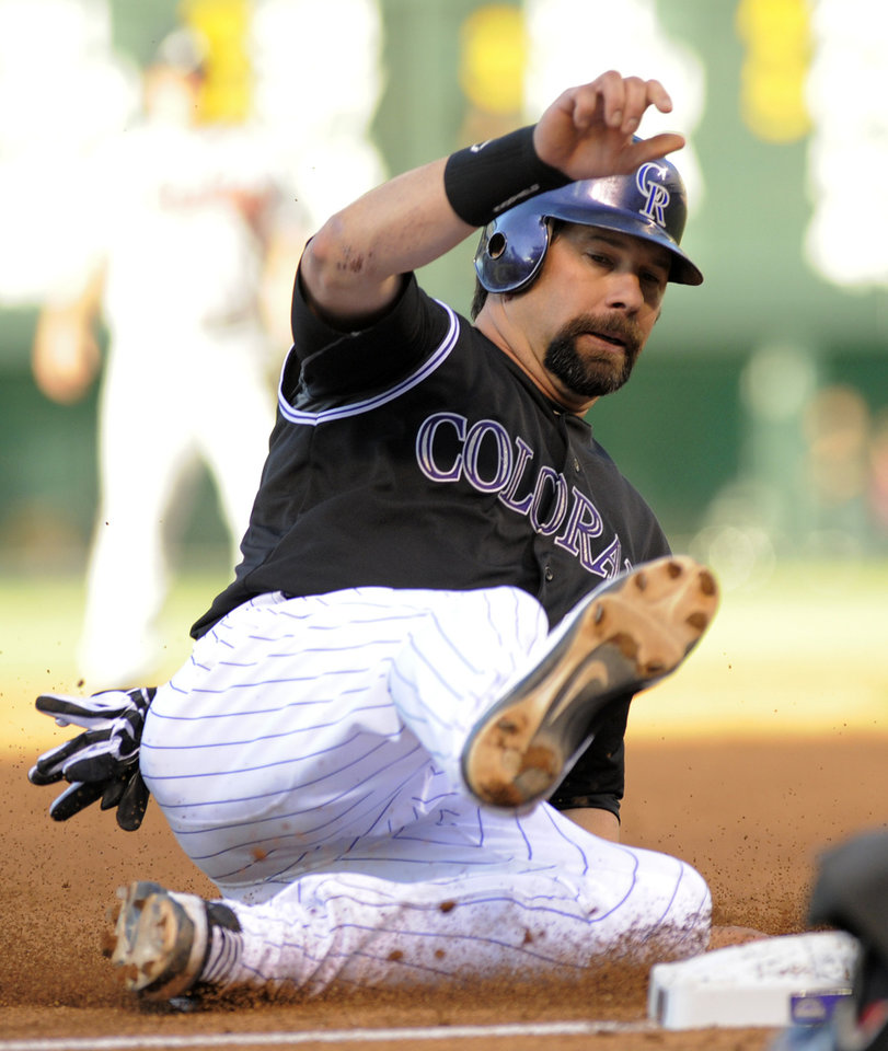 Photo -   Colorado Rockies' Todd Helton slides safe into third during the first inning of a baseball game against the Atlanta Braves, Friday, May 4, 2012, in Denver. (AP Photo/Jack Dempsey)