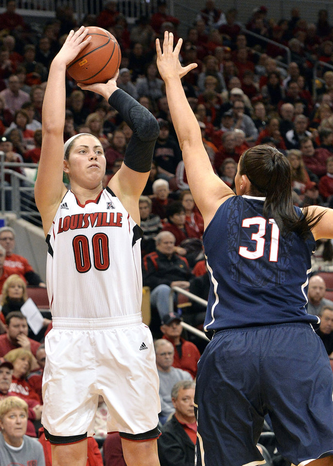 Photo - Louisville's Sara Hammond, left, puts up a shot over the defense of Connecticut's Stefanie Dolson during the first half of an NCAA college basketball game, Monday, March 3, 2014, in Louisville, Ky. (AP Photo/Timothy D. Easley)