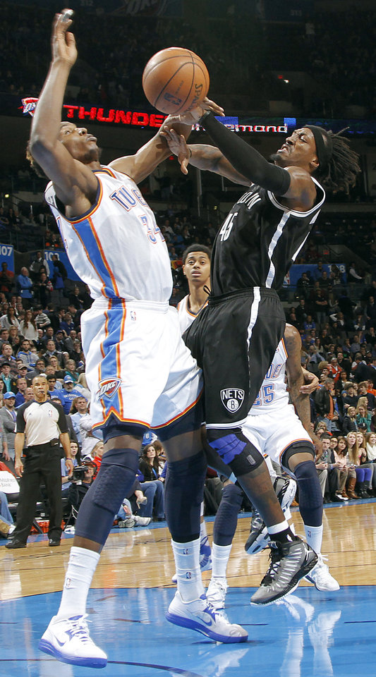 Photo - Oklahoma City's Hasheem Thabeet (34) battles for the ball with Brooklyn Nets' Gerald Wallace (45) during the NBA basketball game between the Oklahoma City Thunder and the Brooklyn Nets at the Chesapeake Energy Arena on Wednesday, Jan. 2, 2013, in Oklahoma City, Okla. Photo by Chris Landsberger, The Oklahoman