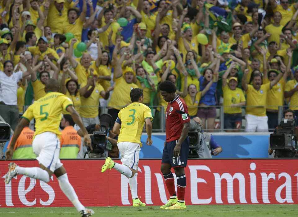 Photo - Brazil's Thiago Silva, center, celebrates after scoring the opening goal during the World Cup quarterfinal soccer match between Brazil and Colombia at the Arena Castelao in Fortaleza, Brazil, Friday, July 4, 2014. (AP Photo/Hassan Ammar)