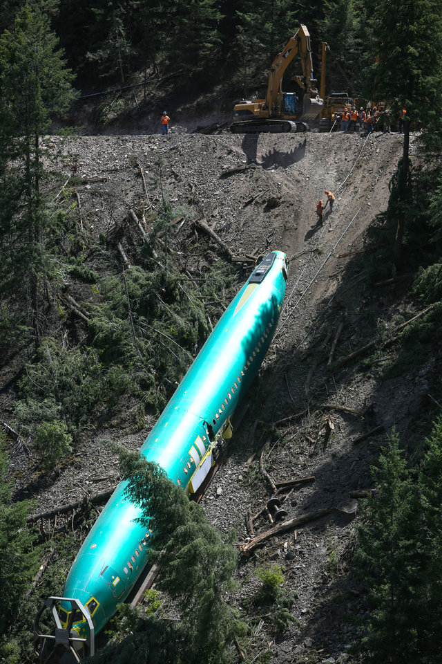 Photo - Work crews remove one of the Boeing 737 fuselages that plunged into the Clark Fork River east of Superior, Mont., on Monday, July 7, 2014. Boeing is deciding what to do with six new commercial airplane bodies that fell off a train in western Montana, including three that slid down a steep riverbank, a company spokeswoman said Monday. (AP Photo/seattlepi.com, Joshua Trujillo) SEATTLE ONLINE OUT; MAGS OUT; NO SALES; SEATTLE TIMES OUT; MANDATORY CREDIT; TV OUT