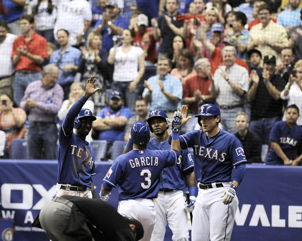 Texas Rangers' Leury Garcia (3) is congratulated on a run by Rangers' Jurickson Profar, left, Jim Adduci, right, and Julio Borbon during an exhibition baseball game against the San Diego Padres, Saturday, March 30, 2013, at the Alamodome in San Antonio. (AP Photo/Darren Abate)
