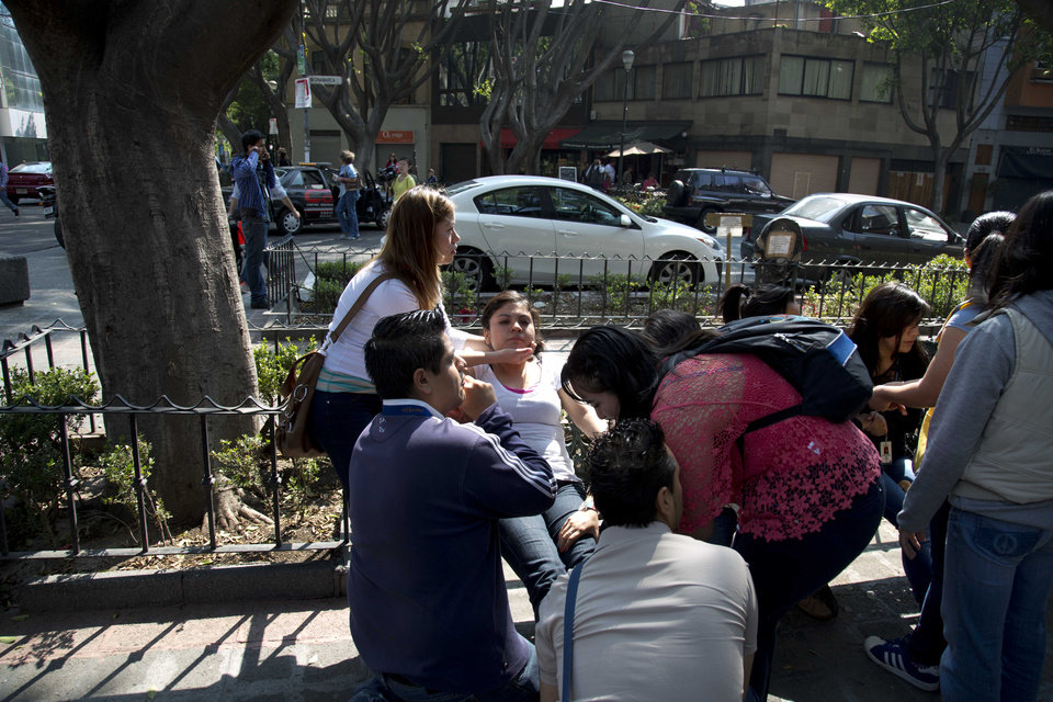 Photo - A woman is comforted by others after a strong earthquake jolted Mexico City, Friday, April 18, 2014. The powerful magnitude-7.2 earthquake shook central and southern Mexico but there were no early reports of major damage or casualties. (AP Photo/Eduardo Verdugo)
