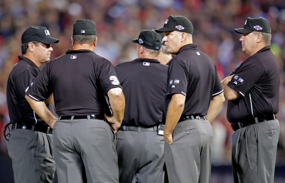 Photo -   Officials stand in the center of the field as fans throw trash during the eighth inning of the National League wild card playoff baseball game between the Atlanta Braves and the St. Louis Cardinals, Friday, Oct. 5, 2012, in Atlanta. The Cardinals won baseball's first wild-card playoff, taking advantage of a disputed infield fly call that led to a protest and fans littering the field with debris to defeat the Braves 6-3. (AP Photo/Todd Kirkland)
