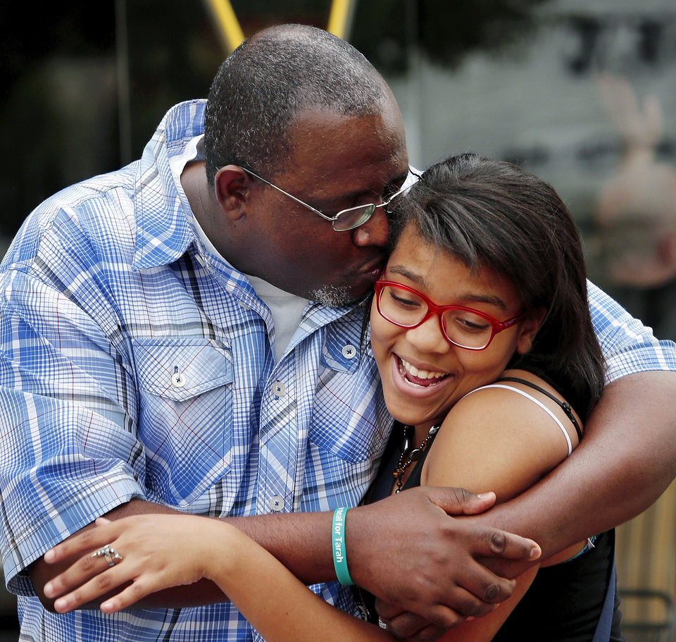 Photo - John Moore, a DHS social worker, hugs his daughter, Travonna, as they leave Midtown restaurant, Kaiser's. Moore and his daughter enjoy spending time together, especially when work doesn't interrupt.  Jim Beckel - THE OKLAHOMAN