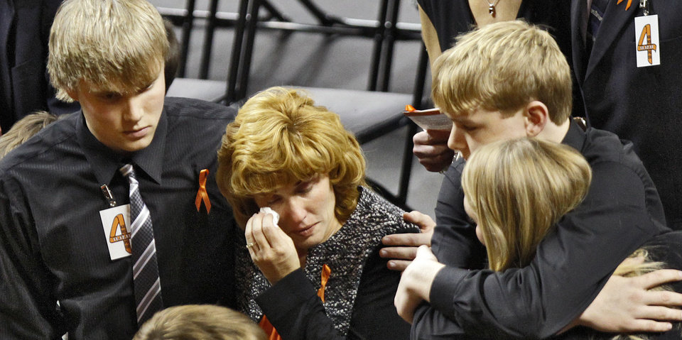 Photo - Alex Budke comforts his mother Shelley as she wipes a tear from her face while with her son Brett and daughter Sara during the memorial service for Oklahoma State head basketball coach Kurt Budke and assistant coach Miranda Serna at Gallagher-Iba Arena on Monday, Nov. 21, 2011 in Stillwater, Okla. The two were killed in a plane crash along with former state senator Olin Branstetter and his wife Paula while on a recruiting trip in central Arkansas last Thursday. Photo by Chris Landsberger, The Oklahoman