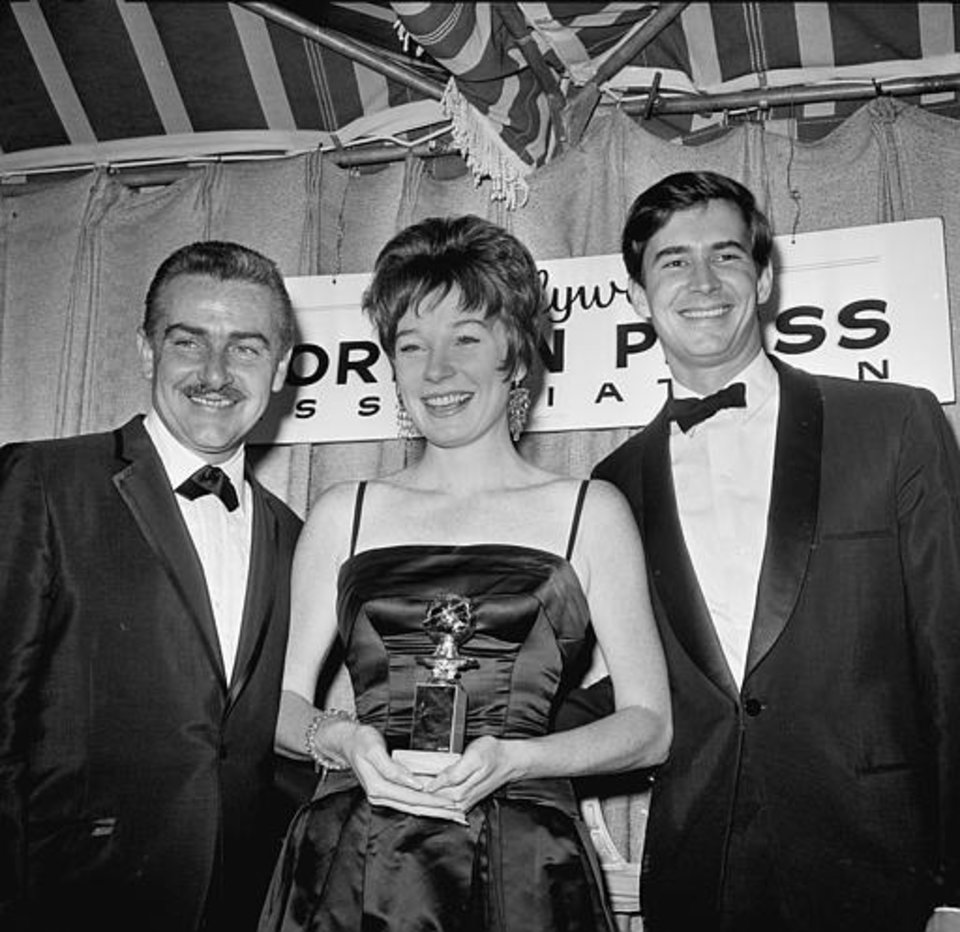 "Actress Shirley MacLaine is flanked by actor Tony Perkins, right, and her husband, producer Steven Parker, left, as she poses with her Golden Globe at the awards presentation on Mach 10, 1964 in Hollywood, California. MacLaine won best actress in a musical or comedy for her performance in ""Irma la Douce.""   (AP Photo)"